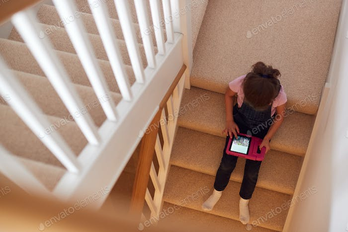 Overhead Shot Of Girl Sitting On Stairs At Home Playing With Digital Tablet
