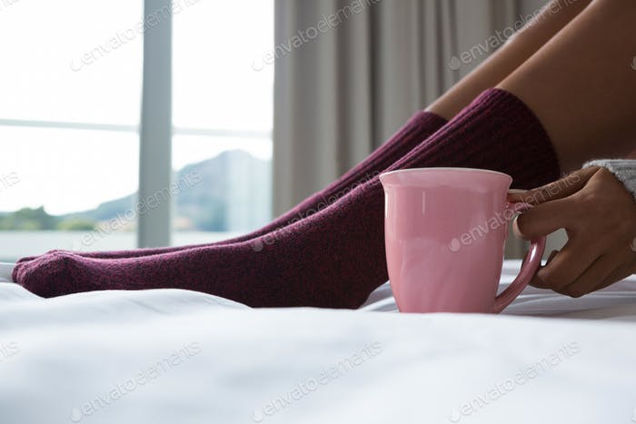 Low section of woman with coffee cup relaxing on bed