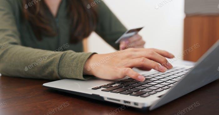 Frau Verwendung von Kreditkarte für Online-Shopping mit Laptop-Computer