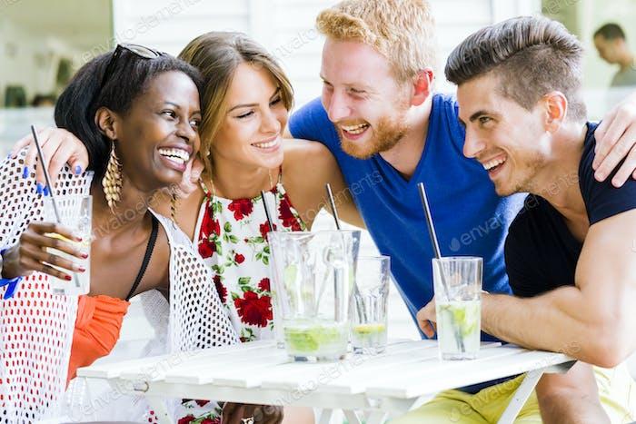 Glückliche junge Leute lachen ein glücklich an einem Tisch