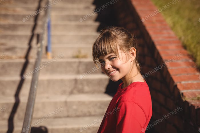 Portrait of happy girl standing near staircase during obstacle course