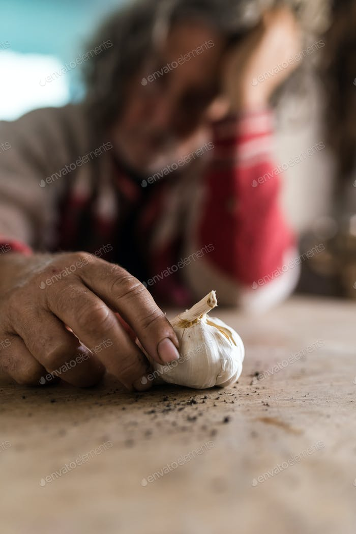 Sad man looking at bulb of garlic holding it with soiled hands