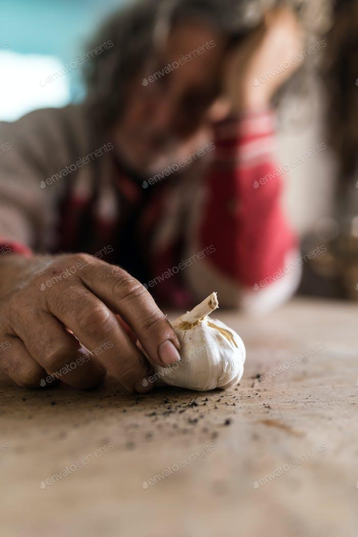 Hombre triste mirando bulbo de ajo sosteniéndolo con las manos sucias