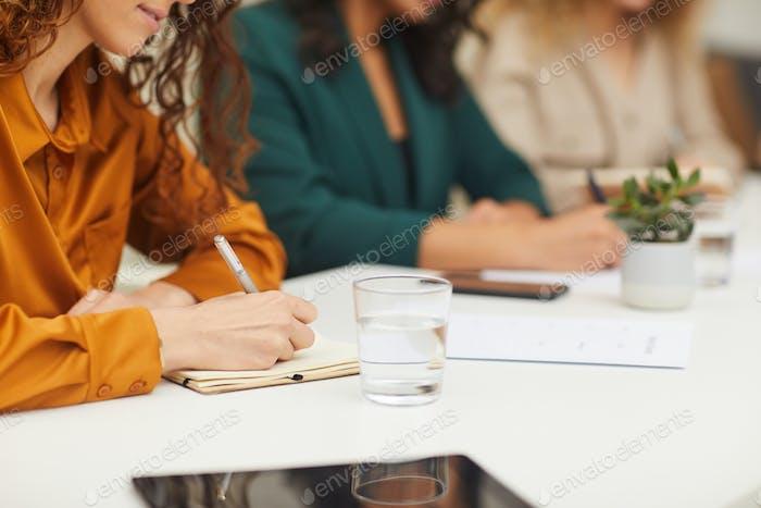 Three Unrecognizable Businesswomen Making Notes
