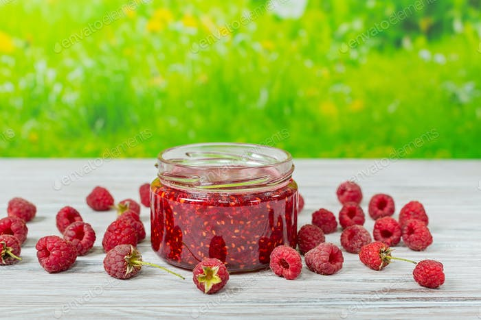 Jam and raspberries on a light wooden table