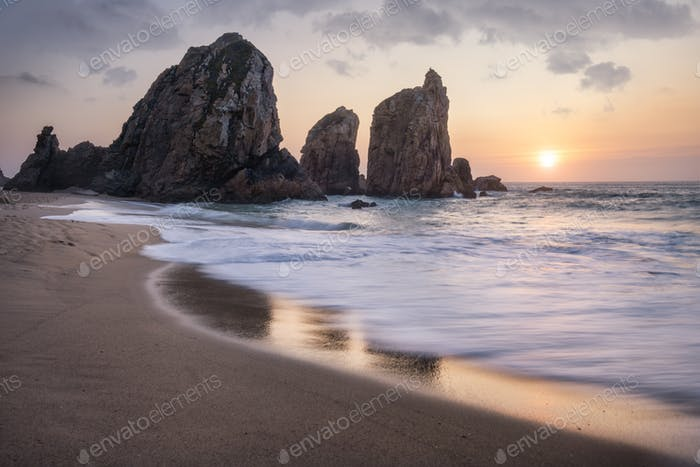 Portugal Ursa Beach. Beautiful sea stacks rocks in sunset light. White atlantic ocean waves on empty