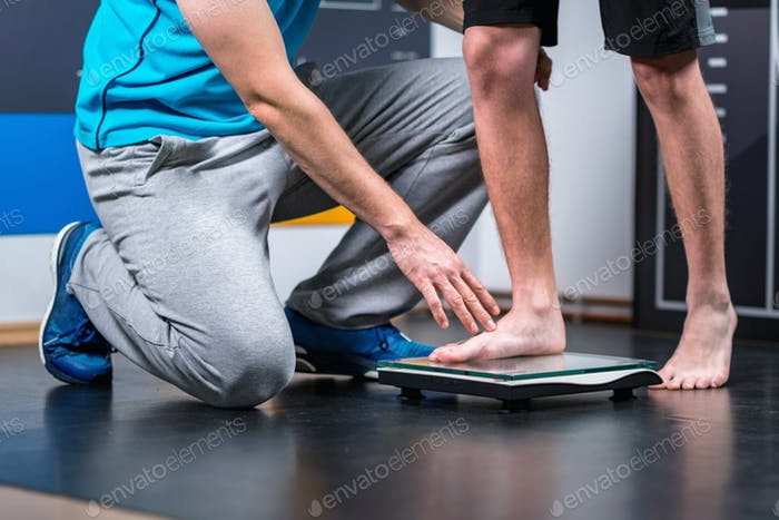 Physical Therapist measuring weight of teenage boy