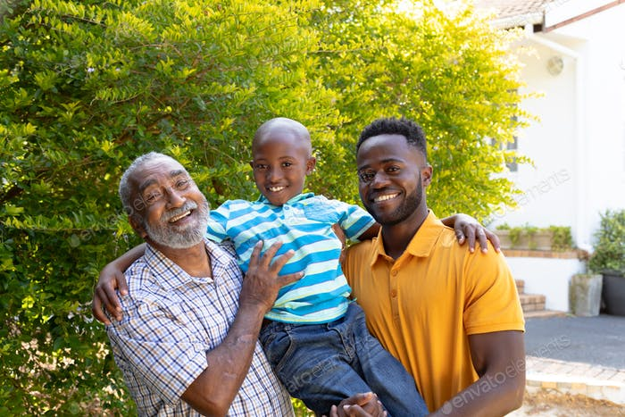 Senior African American man spending time with his son and his grandson in the garden