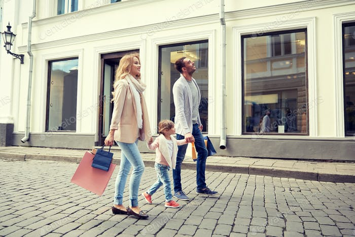 happy family with child and shopping bags in city