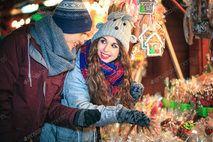 Christmas market shopping, couple choosing things for buying