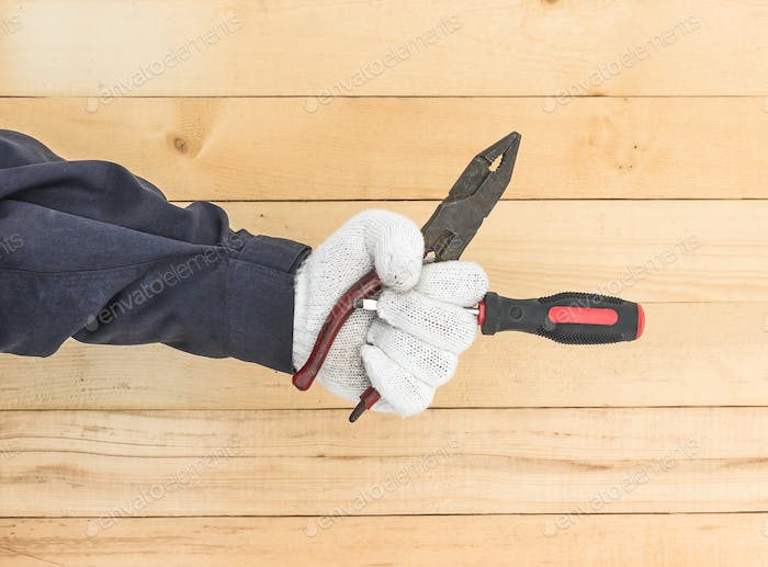 Hand in glove holding screwdriver and pliers