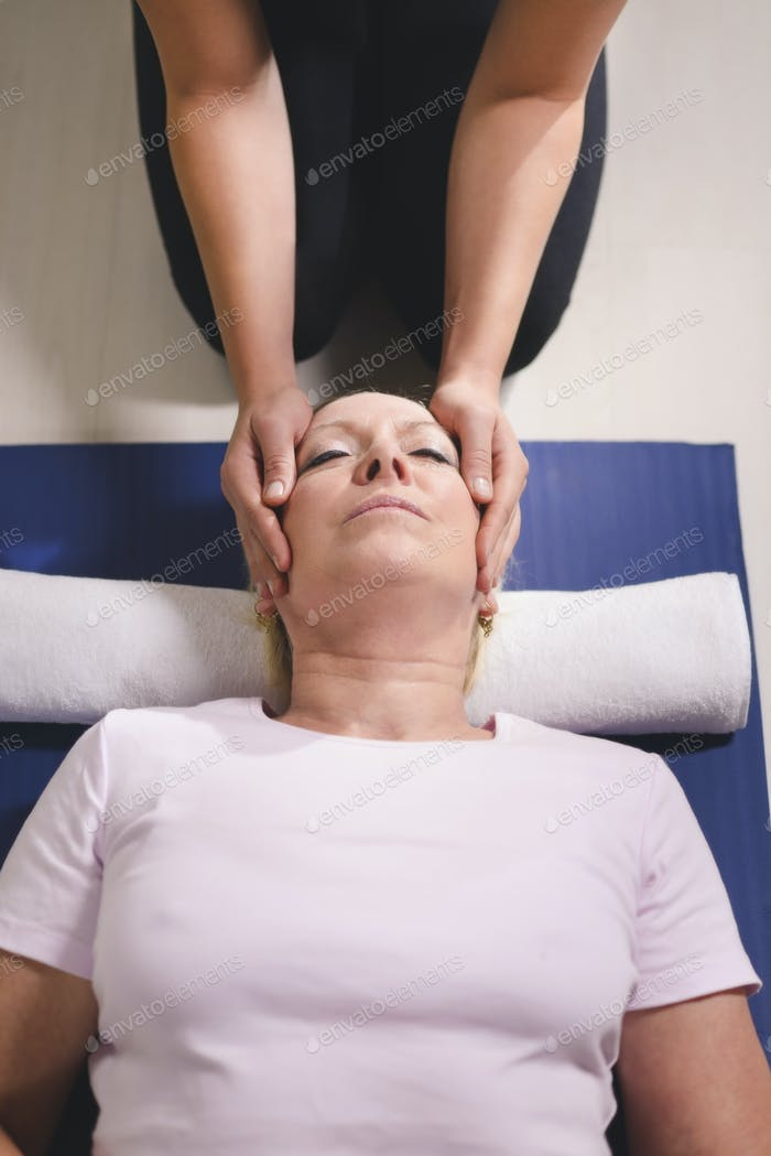 Therapist Doing Reiki Therapy To Senior Woman
