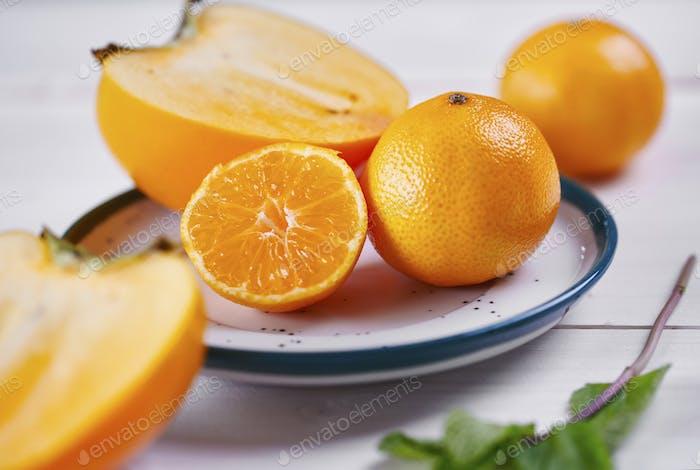 Kaki and oranges on plate