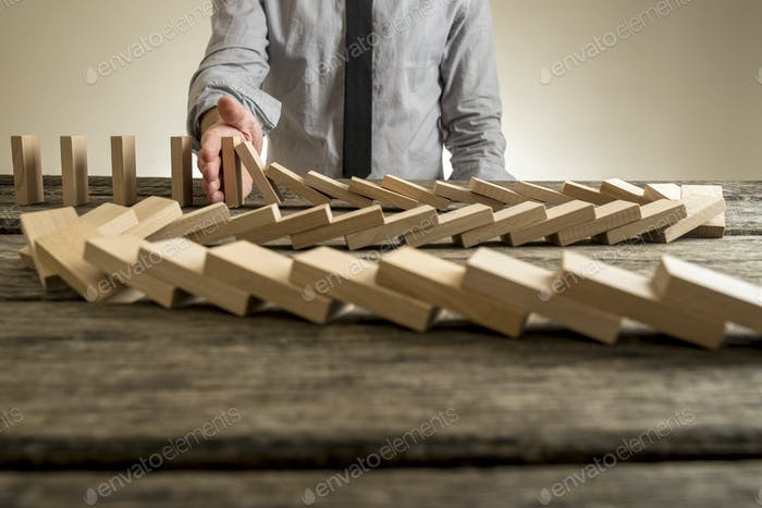 Hand stopping domino effect of wooden blocks