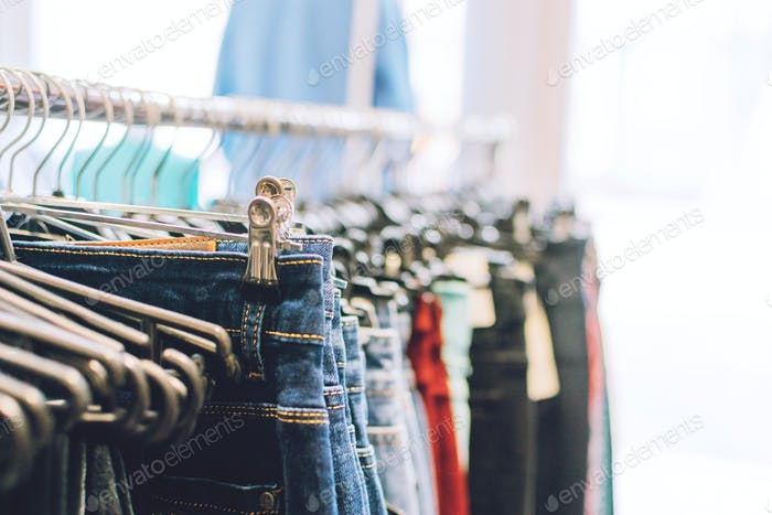 Colorful trend women dresses, pants on hangers in retail shop, store. Fashion and shopping concept