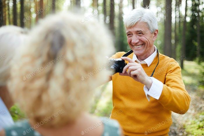 Jolly senior man photographing friends on camera