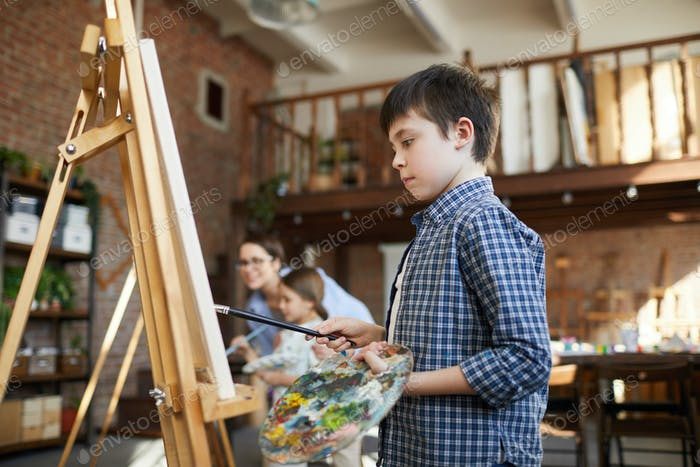 Schoolboy Painting at Easel