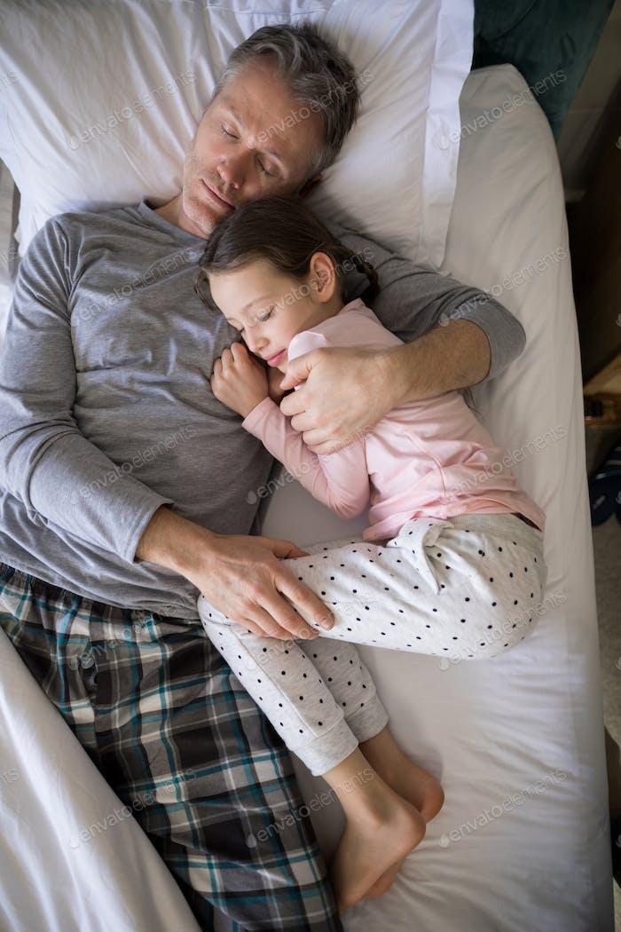 Vater und Tochter schlafen zusammen auf dem Bett im Schlafzimmer