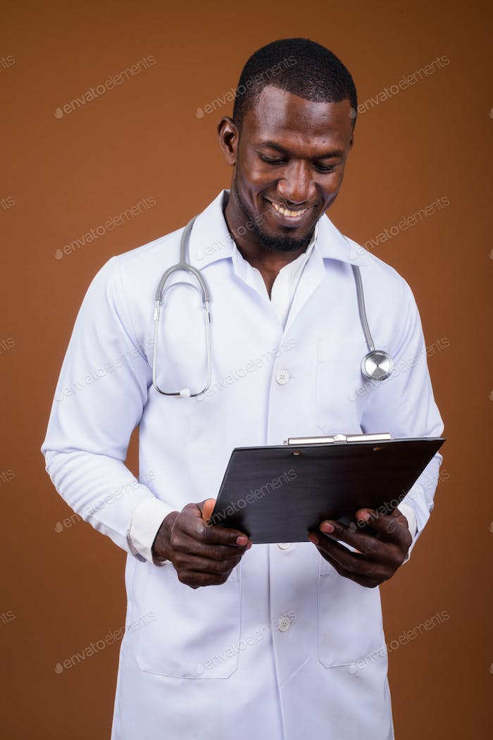 Handsome African man doctor against brown background