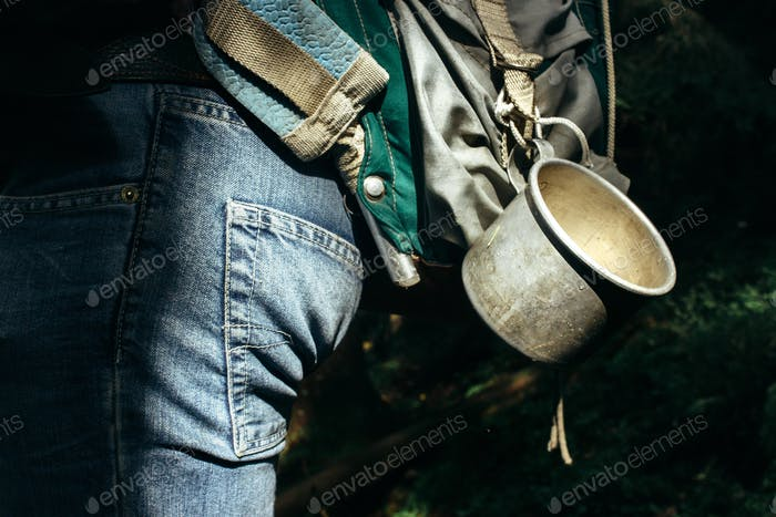 stylish metal cup on traveler backpack in sunny forest in the mountains