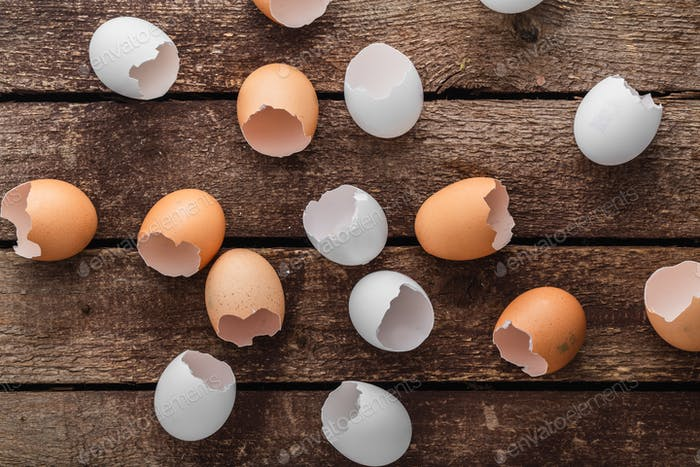 Empty egg shells on wooden background, top view