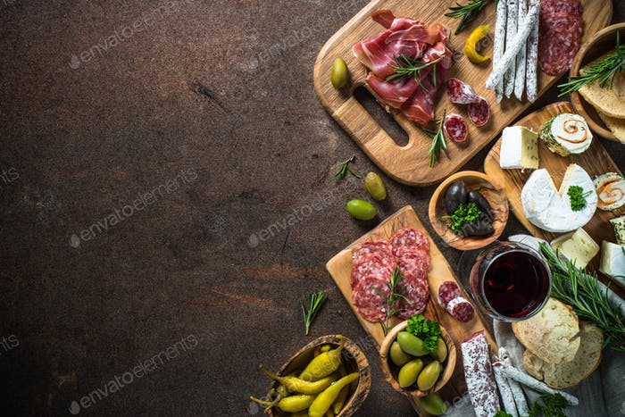 Antipasto delicatessen - meat, cheese, olives and wine on stone