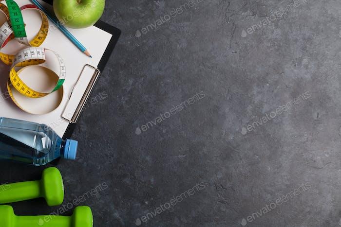 Fitnesskonzept Hanteln, Wasserflasche und Apfel