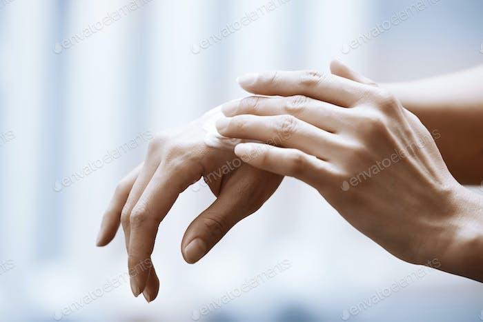 Woman applying moisturizing cream on hands