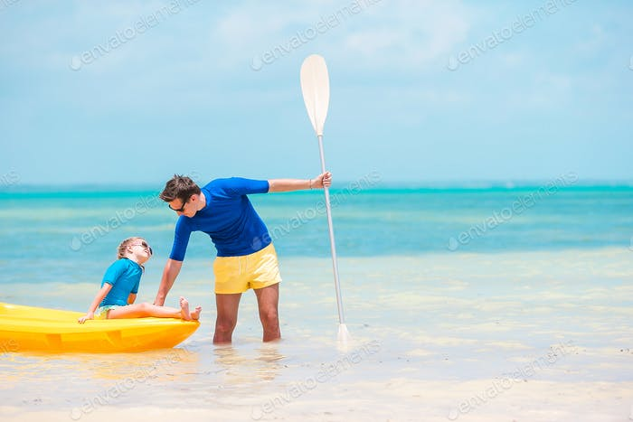 Young father and little kid kayaking at the sea