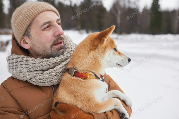 Reifer Mann hält Hund im Winter