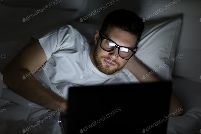young man with laptop in bed at home bedroom