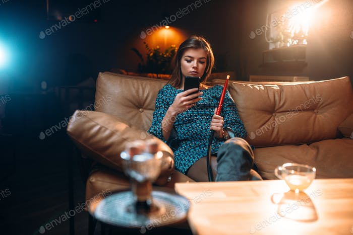 Young woman relaxation, smoking hookah at the bar