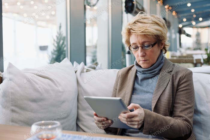 Mid age woman with tablet sitting cafe