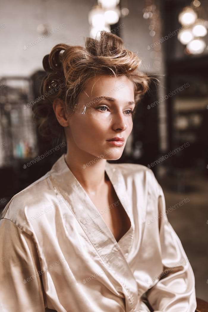 Young beautiful pensive woman with wavy hairstyle in silk robe d