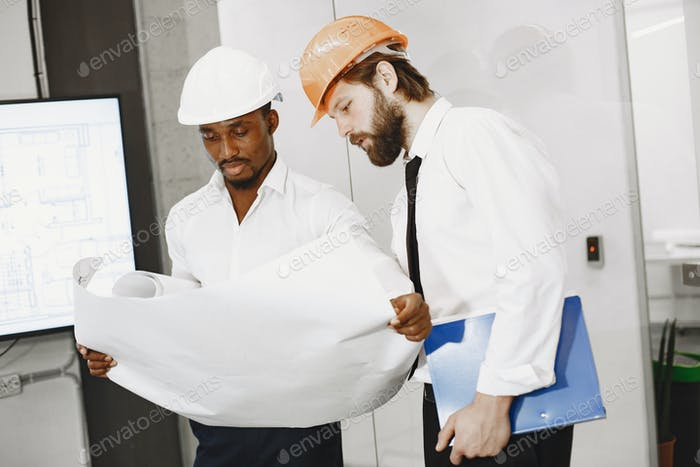 Two managers in the office with helmets