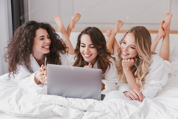 Three gorgeous women 20s wearing white bathrobe lying in luxury