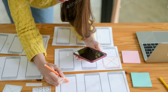 The young designer is sketching a smartphone screen and an app.