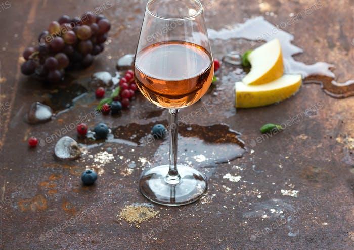 Glas Rosenwein mit Beeren, Melone, Trauben und Eis auf grunge rostigen Metallhintergrund