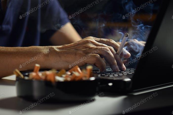Человек держит горит и курение сигареты между пальцами и работает на ноутбуке