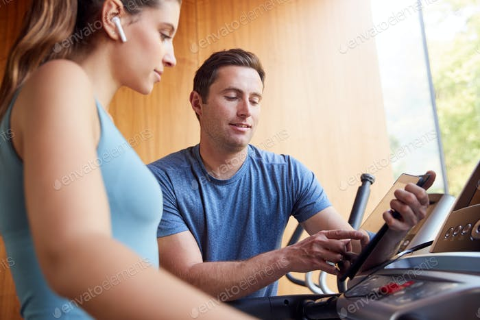 Woman In Gym With Personal Trainer Analysing Performance Using Smart Watch And Digital Tablet