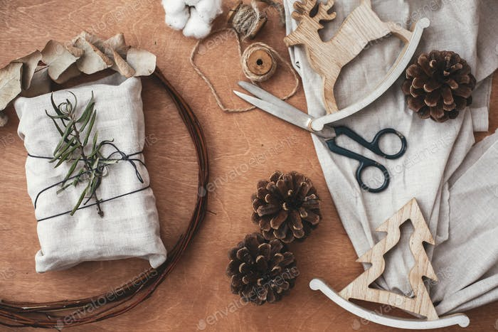 Stylish rustic gift wrapped in linen fabric with green branch on wooden table