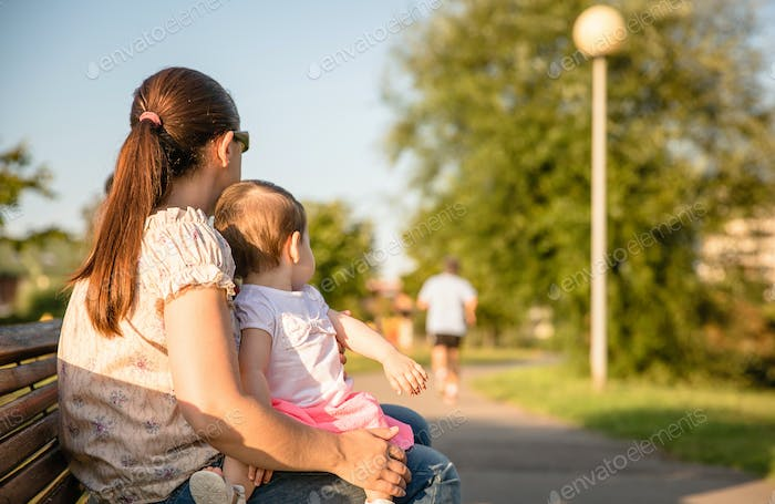 Baby girl and woman sitting on a park bench