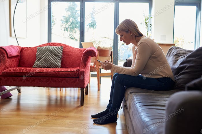 Woman Sitting On Sofa Sending Text Message On Phone