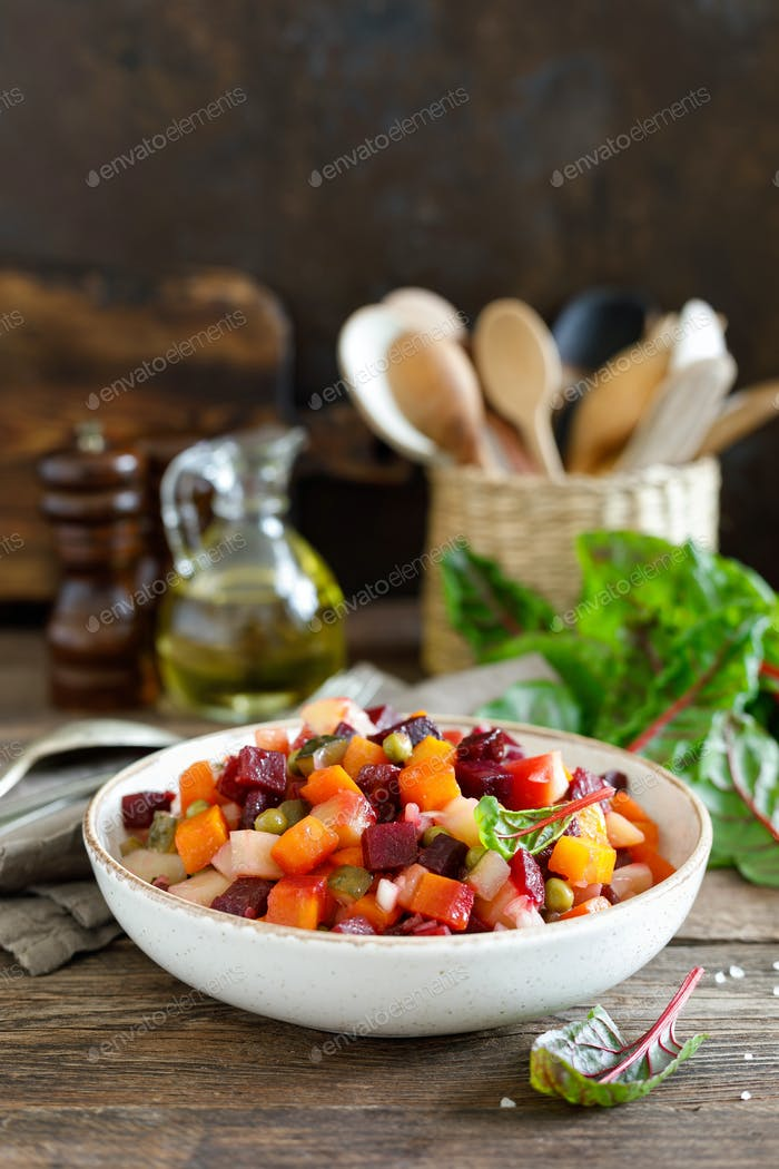 Beetroot or beet salad with boiled vegetables on wooden rustic table closeup