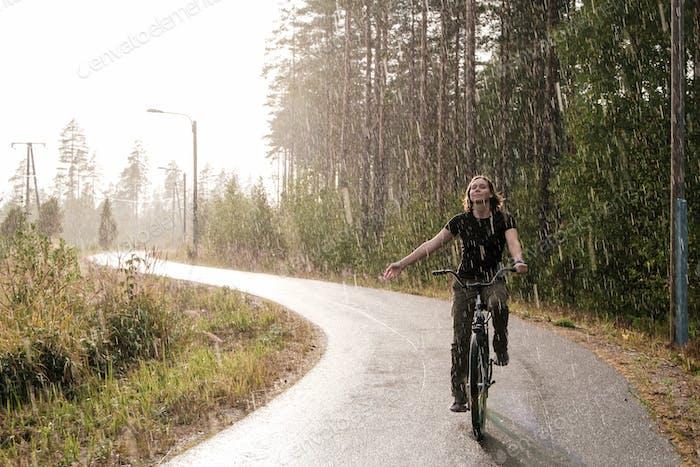 A woman riding a bike and enjoying a warm summer rain