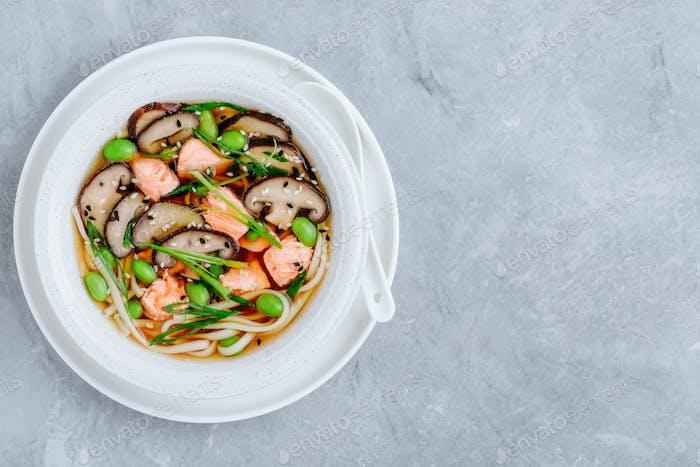 Lachs-Nudelsuppe mit Shiitake-Pilzen, Edamame-Bohnen und Frühlingszwiebeln.