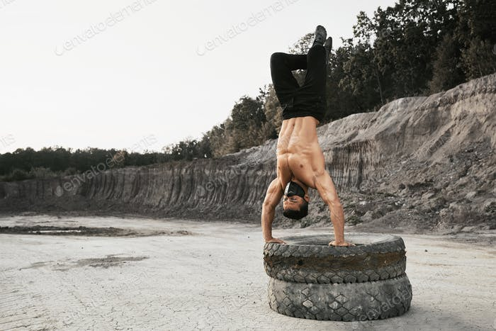 Strong man doing handstand on tyres outdoors