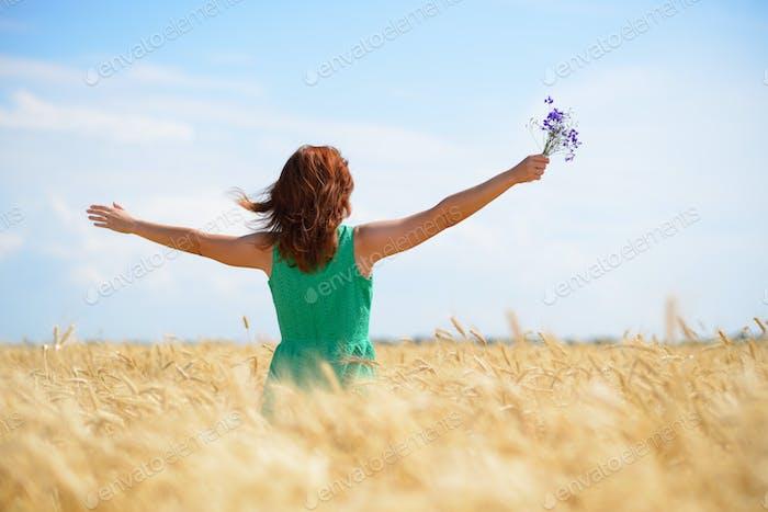 Woman enjoying sunlight on wheat field