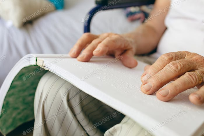 Mid section of senior Caucasian male patient is reading in braille in retirement home
