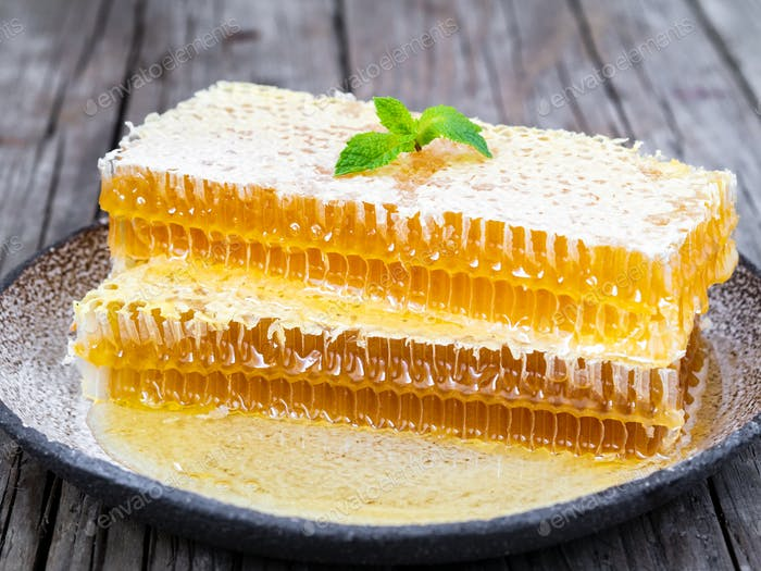 honey in honeycomb, close-up, on white ceramic plate, on wooden rustic table, side view, sunlight
